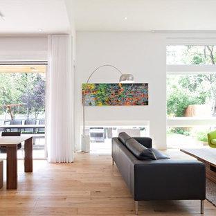 Mittelgroßes, Repräsentatives, Abgetrenntes Modernes Wohnzimmer mit weißer Wandfarbe, hellem Holzboden, Tunnelkamin, verputzter Kaminumrandung, Wand-TV und beigem Boden in Calgary