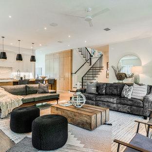 Diseño de salón abierto, actual, grande, con paredes blancas, suelo de madera clara, chimenea tradicional, marco de chimenea de hormigón y televisor colgado en la pared