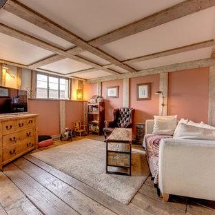 Modelo de salón para visitas abierto, campestre, con paredes rosas, suelo de madera en tonos medios y televisor independiente