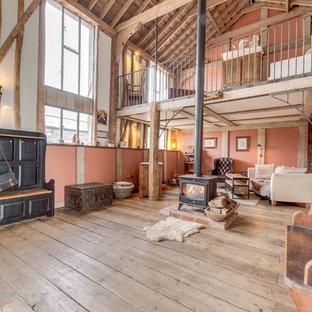 Idee per un ampio soggiorno country con pareti rosa e parquet chiaro
