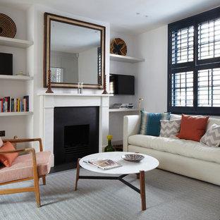 Immagine di un piccolo soggiorno chic aperto con libreria, pareti bianche, moquette, camino classico e cornice del camino in metallo