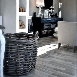 Foto de salón para visitas abierto, actual, grande, sin chimenea, con paredes grises, suelo laminado y televisor colgado en la pared