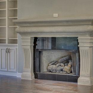 Idee per un grande soggiorno chic aperto con pareti grigie, pavimento in gres porcellanato, camino classico e cornice del camino in cemento