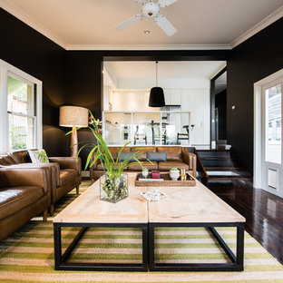 This is an example of a transitional enclosed living room in Sydney with black walls and dark hardwood floors.