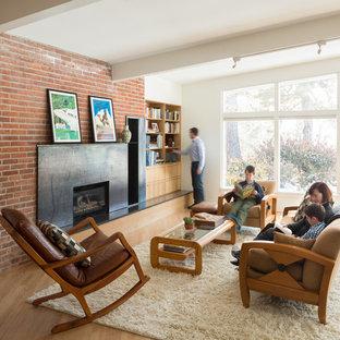 Idee per un soggiorno minimalista chiuso con libreria, pareti bianche, parquet chiaro, camino classico, cornice del camino in metallo e nessuna TV