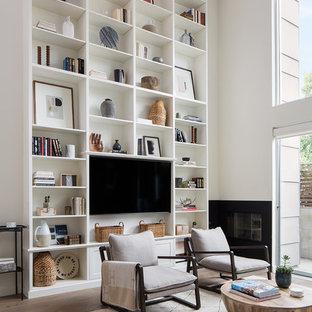 Immagine di un grande soggiorno boho chic stile loft con pareti bianche, parquet chiaro, camino classico, cornice del camino in metallo, parete attrezzata e pavimento marrone