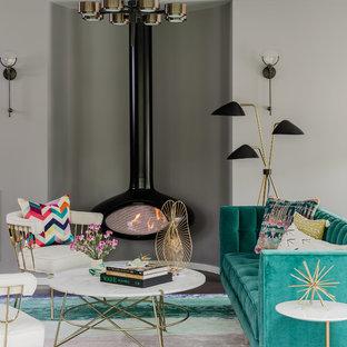 Foto di un soggiorno eclettico di medie dimensioni e chiuso con sala formale, pareti grigie, pavimento in legno massello medio, camino sospeso e pavimento marrone