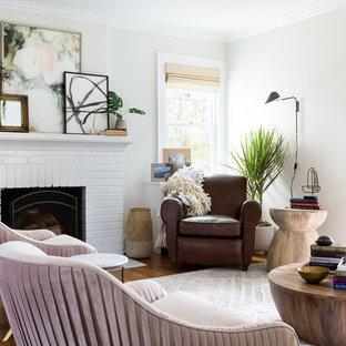 Modelo de salón para visitas cerrado, ecléctico, pequeño, sin televisor, con paredes blancas, suelo de madera en tonos medios, chimenea tradicional, marco de chimenea de ladrillo y suelo marrón