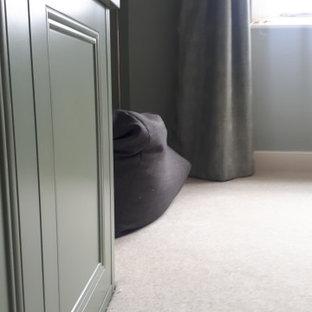 Idee per un grande soggiorno stile americano chiuso con pareti verdi, moquette, stufa a legna, cornice del camino in mattoni, TV autoportante, pavimento beige e pareti in mattoni