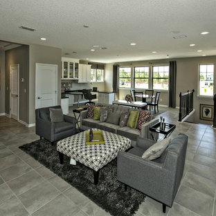 Example of a huge trendy loft-style ceramic floor living room design in Jacksonville with a bar, gray walls, no fireplace and a wall-mounted tv