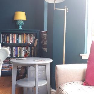 Ispirazione per un grande soggiorno moderno chiuso con pareti verdi, pavimento in legno massello medio, stufa a legna, cornice del camino in cemento e TV autoportante