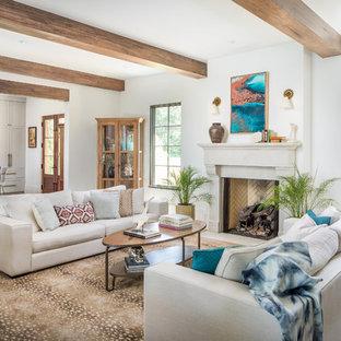 Modelo de salón abierto, mediterráneo, con suelo de madera en tonos medios, paredes blancas, chimenea tradicional y suelo marrón