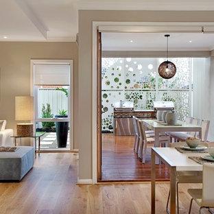 Esempio di un soggiorno contemporaneo aperto con pareti beige e pavimento in legno massello medio