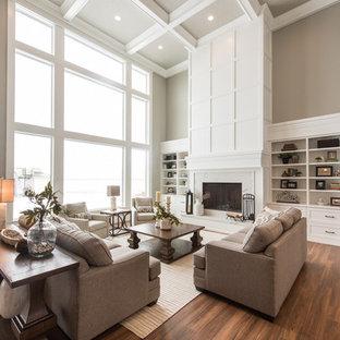 ソルトレイクシティのトランジショナルスタイルのおしゃれなLDK (ベージュの壁、無垢フローリング、標準型暖炉、木材の暖炉まわり、茶色い床) の写真