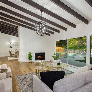 Réalisation d'un salon vintage ouvert avec un mur blanc, un sol en bois brun, une cheminée standard, un manteau de cheminée en brique, un sol marron, un plafond en poutres apparentes, un plafond en lambris de bois et un plafond voûté.