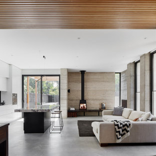 Inspiration for a mid-sized contemporary open concept living room in Melbourne with white walls, concrete floors, a wood stove and grey floor.