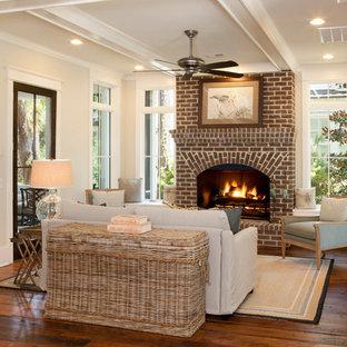 チャールストンの中サイズのビーチスタイルのおしゃれな独立型リビング (ベージュの壁、無垢フローリング、標準型暖炉、レンガの暖炉まわり) の写真