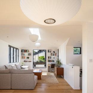 Idéer för ett mellanstort modernt allrum med öppen planlösning, med vita väggar, ljust trägolv och en dold TV