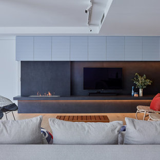 Inspiration for a large contemporary open concept living room in Sydney with light hardwood floors, a wall-mounted tv, brown floor, white walls and a ribbon fireplace.