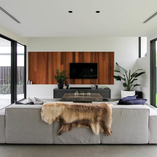 This is an example of a contemporary enclosed living room in Sunshine Coast with white walls, concrete floors, a wall-mounted tv and grey floor.