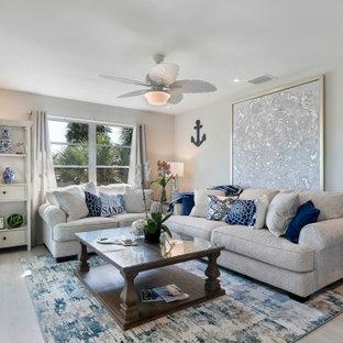 マイアミの小さいビーチスタイルのおしゃれなLDK (白い壁、淡色無垢フローリング、暖炉なし、壁掛け型テレビ、ベージュの床) の写真