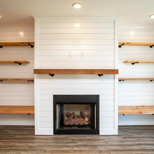 Idée de décoration pour un salon de taille moyenne et ouvert avec un mur gris, un sol en vinyl, une cheminée standard, un manteau de cheminée en lambris de bois, un téléviseur fixé au mur, un sol gris et du lambris de bois.