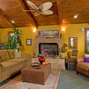 Immagine di un soggiorno rustico di medie dimensioni con pareti gialle, pavimento in ardesia, camino classico e cornice del camino in cemento