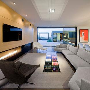 Diseño de salón abierto, minimalista, con paredes blancas, chimenea lineal, suelo de cemento y televisor colgado en la pared