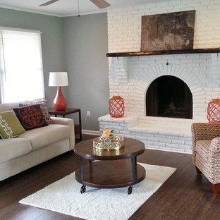 Idee per un piccolo soggiorno tradizionale aperto con pareti grigie, parquet scuro, camino classico, cornice del camino in mattoni, nessuna TV, sala formale e pavimento marrone