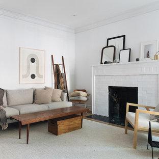 Immagine di un soggiorno nordico di medie dimensioni e aperto con pareti bianche, pavimento in legno massello medio, camino classico e cornice del camino in mattoni