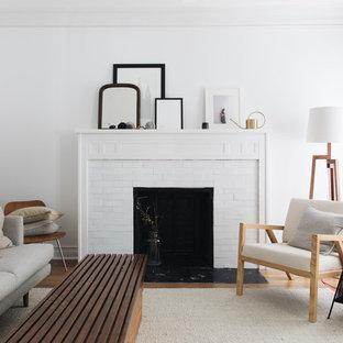 Immagine di un soggiorno nordico di medie dimensioni con pareti bianche, camino classico e parquet chiaro