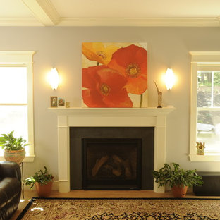 This is an example of a traditional open concept living room in Portland Maine with grey walls, vinyl floors, a standard fireplace, a wood fireplace surround and no tv.
