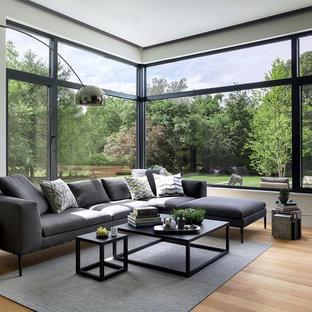 Modelo de salón tipo loft, moderno, grande, sin chimenea, con paredes blancas, suelo de madera en tonos medios y suelo beige