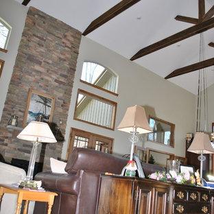 Immagine di un grande soggiorno stile rurale aperto con pareti beige, pavimento in ardesia, camino classico, cornice del camino in pietra e pavimento nero