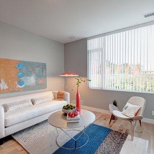 Ejemplo de salón abierto, moderno, pequeño, sin chimenea, con paredes grises, suelo de madera clara y televisor colgado en la pared