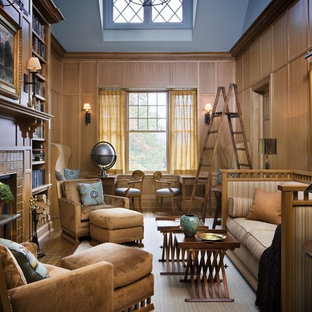 Inredning av ett klassiskt mycket stort vardagsrum, med ett bibliotek, bruna väggar, ljust trägolv, en standard öppen spis och en spiselkrans i trä