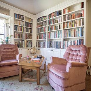 Diseño de biblioteca en casa abierta, clásica, grande, con paredes blancas, suelo laminado, pared multimedia y suelo marrón