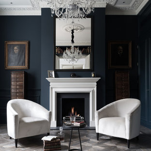 Photo of a medium sized traditional formal enclosed living room in London with blue walls, a standard fireplace and grey floors.