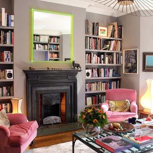 Cette photo montre un salon avec une bibliothèque ou un coin lecture éclectique de taille moyenne et ouvert avec un mur gris, une cheminée standard, un manteau de cheminée en métal, un sol en marbre et un sol marron.