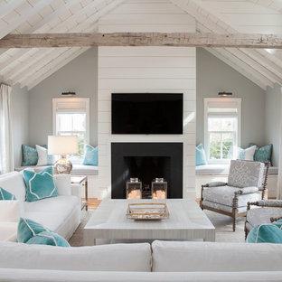 Exempel på ett stort maritimt allrum med öppen planlösning, med ett finrum, grå väggar, en standard öppen spis, en väggmonterad TV och ljust trägolv