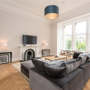 Photo of a medium sized contemporary enclosed living room in Edinburgh with grey walls, light hardwood flooring, a standard fireplace, a wall mounted tv and beige floors.