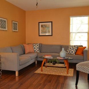 Immagine di un soggiorno moderno di medie dimensioni e aperto con sala formale, pareti arancioni, pavimento in legno massello medio, nessun camino e nessuna TV