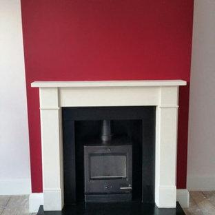 ロンドンの中サイズのヴィクトリアン調のおしゃれなリビング (赤い壁、濃色無垢フローリング、薪ストーブ、石材の暖炉まわり) の写真