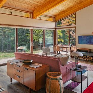 Foto på ett mellanstort 50 tals allrum med öppen planlösning, med vita väggar, mellanmörkt trägolv, en standard öppen spis, en spiselkrans i trä och en väggmonterad TV