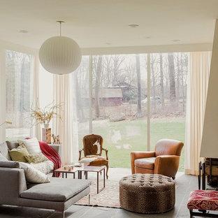 Foto på ett stort funkis allrum med öppen planlösning, med ett finrum, vita väggar, skiffergolv, en standard öppen spis, en spiselkrans i sten och grått golv