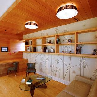 Idée de décoration pour un petit salon design fermé avec un sol en bois clair, aucune cheminée, un mur beige et aucun téléviseur.