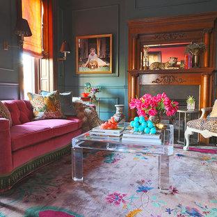 Idée de décoration pour un très grand salon bohème ouvert avec une salle de musique, un mur bleu, un sol en bois foncé, une cheminée standard, un manteau de cheminée en pierre et un téléviseur fixé au mur.