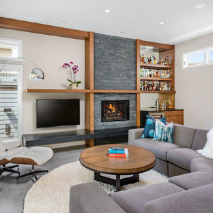 Large contemporary living room in Chicago with a home bar, beige walls, a wall mounted tv, a standard fireplace, porcelain flooring and a stone fireplace surround.
