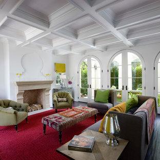 Modelo de salón para visitas mediterráneo con paredes blancas, suelo de madera oscura, chimenea tradicional y marco de chimenea de baldosas y/o azulejos
