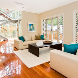 This is an example of a contemporary formal open concept living room in Sydney with beige walls and medium hardwood floors.